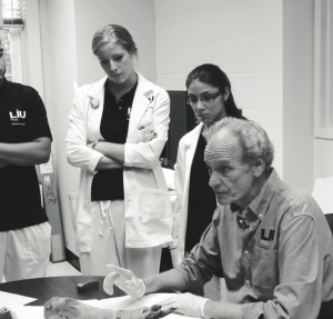 Dr. Bob Brier examines an arm from an Egyptian mummy with LIU Post students in the Medical Imaging Lab. By LIU Post PR