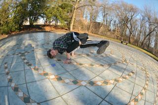 A student break-dances on the Labyrinth located next to the Winnick Mansion