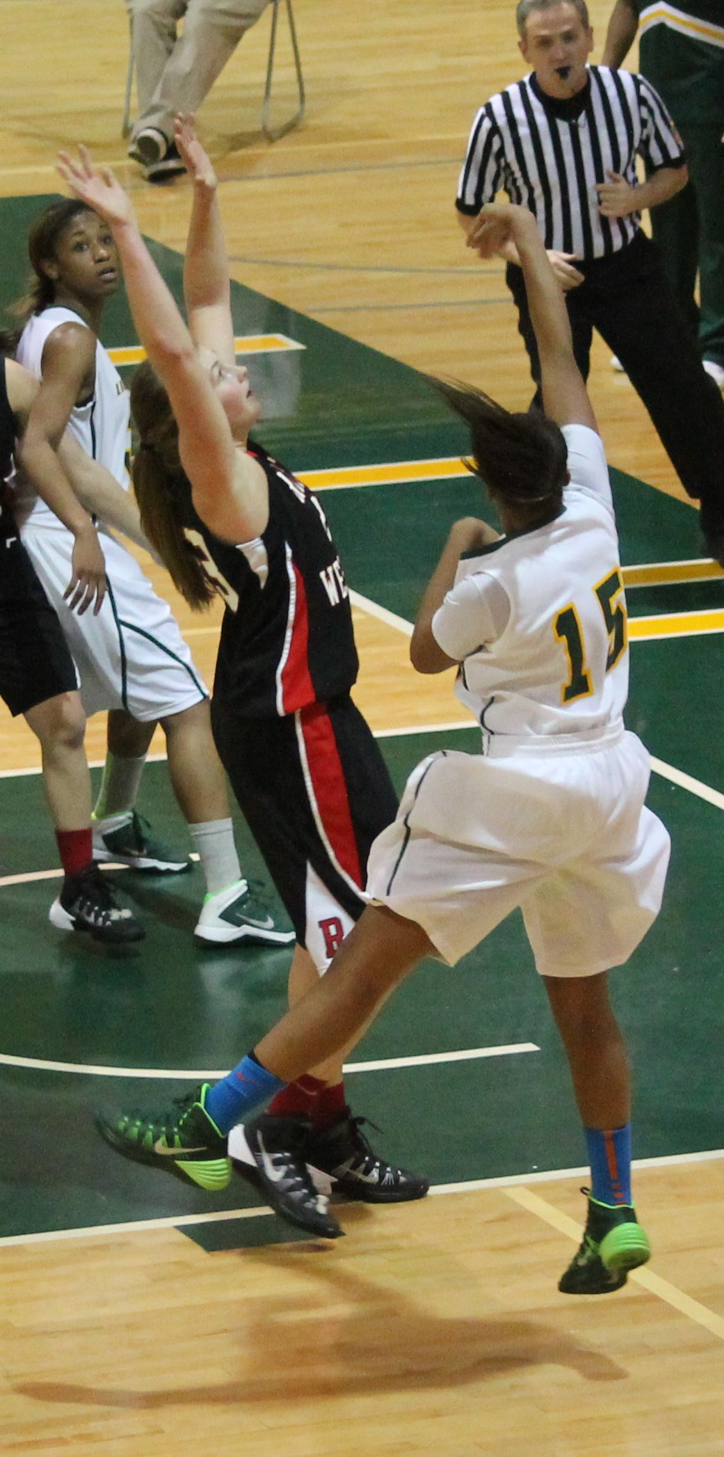 Senior point guard Chelsea Williams, #15, sinks a shot for the Green and Gold. Photo by Kimeberly Toledo