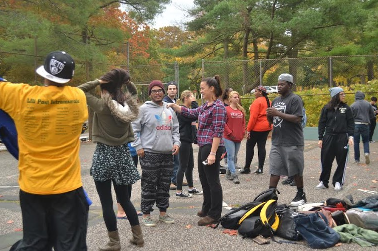 Students participate in a service project to restore the basketball courts on campus. Photo by Janisha Sanford