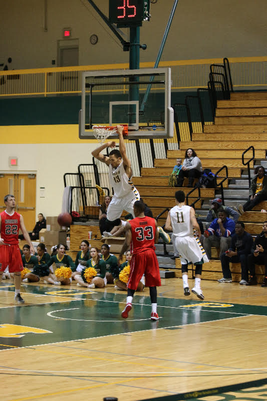 #13 freshman guard Aary Bibens dunks a two-pointer for the Pioneers. Photo: Kimberly Toledo