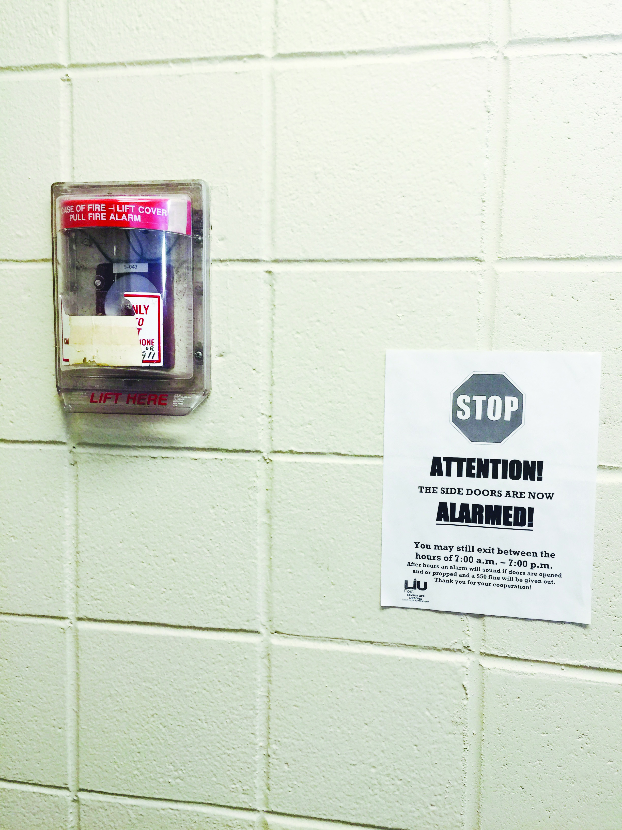 A flyer in Brookville Hall informs residents about the new door alarm system, which is equipped with security cameras. Photo: Tyler Tarae Hutchins